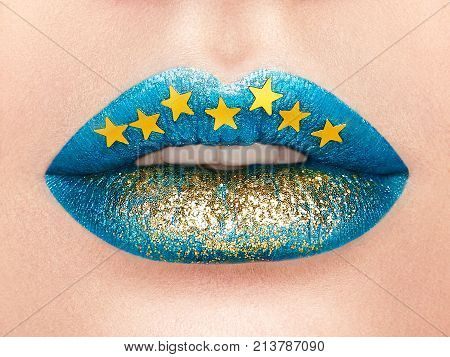 Close up view of Beautiful Woman Lips with blue Lipstick. Open Mouth with white Teeth. Cosmetology drugstore or Fashion Makeup Concept Gold stars. Beauty studio shot. Passionate Kiss