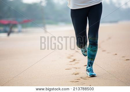 Woman Is Jogging Along The Seashore On An Overcast Day