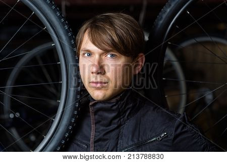Portrait Of A Handsome Man With Bicycle Wheels Closeup