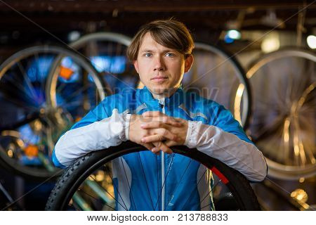 Portrait of a cyclist in garage with bicycles behind him