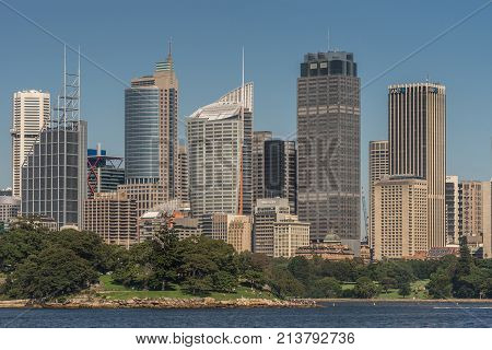 Sydney Australia - March 26 2017:Closeup kind of shot of selection of tall office towers skyline seen off the water under blue sky. Botanical garden.