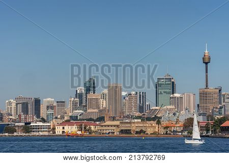 Sydney Australia - March 26 2017: Closeup kind of shot of selection of tall office towers skyline seen off the water under blue sky. White sail boat Navy ship and spires of Saint Mary Cathedral.
