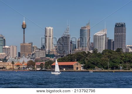Sydney Australia - March 26 2017: Closeup kind of shot of selection of tall office towers skyline seen off the water under blue sky. White sail boat Navy ship.