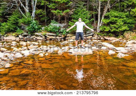 Young man with outstretched arms meditating enjoying nature on peaceful calm Red Creek river in Dolly Sods West Virginia during sunny day with reflection