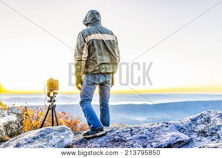 Standing young man photographer with camera and tripod on cold autumn morning in jacket in Bear Rocks West Virginia taking pictures of sunrise