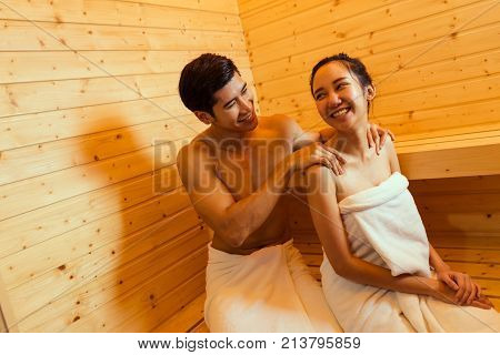 Couple at sauna spa healthy concept Young asian man handsome and woman beautiful together sitting massage in room with hot warm steam happy relaxing resting for health care and skin in holiday