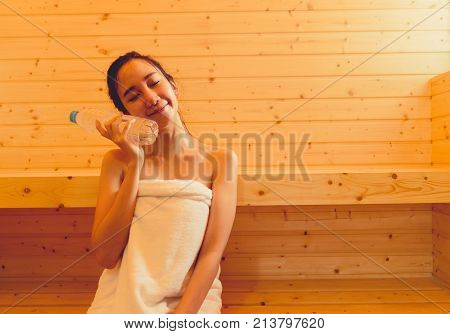 Young asian woman in sauna spa room with hot warm steam holding water bottle happy relaxing resting for health care and skin in holiday