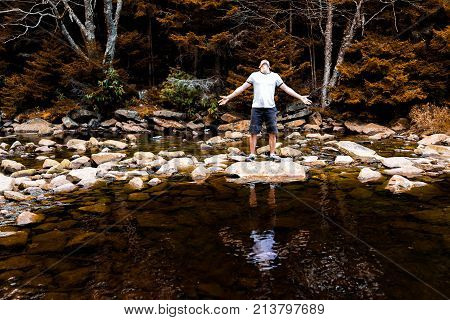 Young Man With Outstretched Arms Meditating Enjoying Nature On Peaceful, Calm Red Creek River In Dol