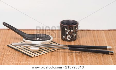 Metal chopsticks on ceramic chopsticks rest, black porcelan spoon with white spoon rest and black sake glass on bamboo mat. White background. Front view