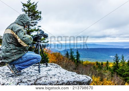 Standing Young Man Photographer With Camera, Gear And Tripod On Cold Autumn Morning In Jacket In Bea