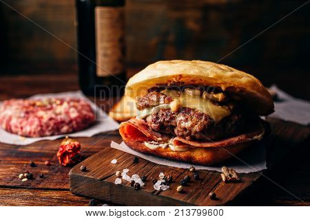Homemade Burger on Cutting Board. Cheeseburger with Beef Patty, Wisconsin Swiss Cheese, Ham, Sauteed Mushrooms, Dijon Mustard, Mayonnaise and Potato Roll. Bottle of Craft Beer on Background.