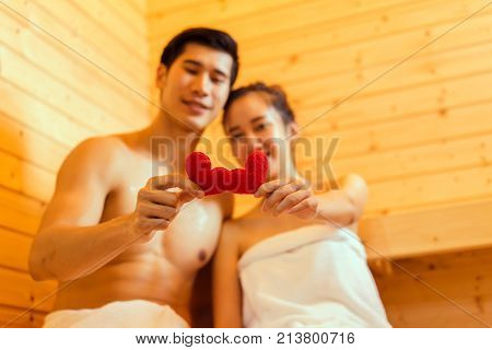 Couple at sauna spa healthy concept Young asian man handsome and woman beautiful together sitting in room with hot warm steam happy relaxing resting for health care and skin in holiday
