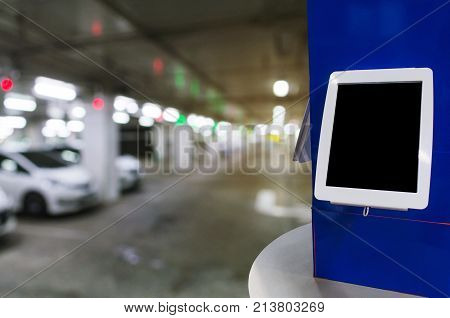 blank digital monitor or tablet on desk at intelligent technology car parking garage area at department store or shopping mall copy space for text or media content marketing advertisement concept