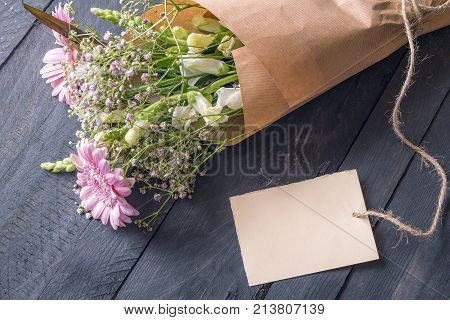 Message card and a bouquet of flowers - Greeting card idea with a cheerful bouquet of flowers wrapped in vintage brown paper and an empty etiquette tied to it on a rustic wooden table.