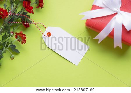 Message card with gift and flowers - Gifting theme image with lovely red flowers an empty label tied to it and a red gift tied with white ribbon and bow on a green background. Greeting card idea.