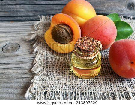 Apricot oil from apricot kernels in a glass jar and fresh ripe apricots on old wooden table.Essential apricot kernel oil for spa,beauty treatment,aromatherapy and bodycare. Selective focus.