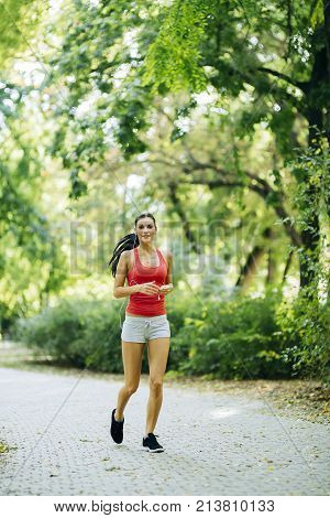 Young beautiful athlete jogging in park and listening to some music while pursuing activity