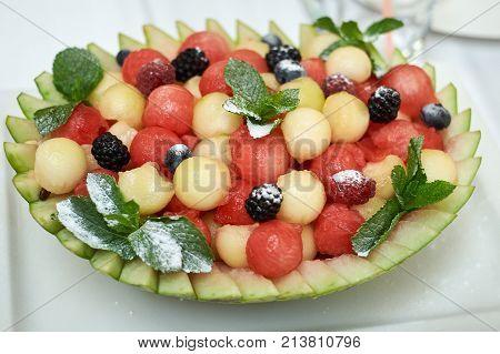 Basket of ripe juicy watermelon balls and sugar powder