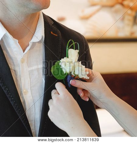 The bride wears a buttonhole for groom.