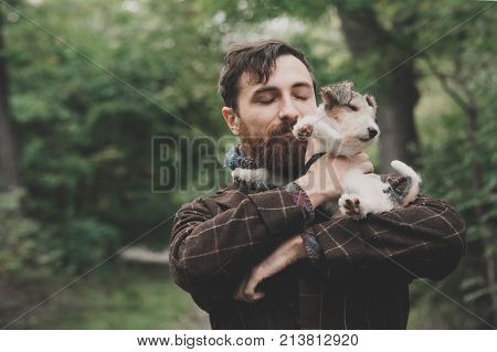 Dog and his owner - Cool dog and young man having fun in a park - Concepts of friendship, pets, togetherness