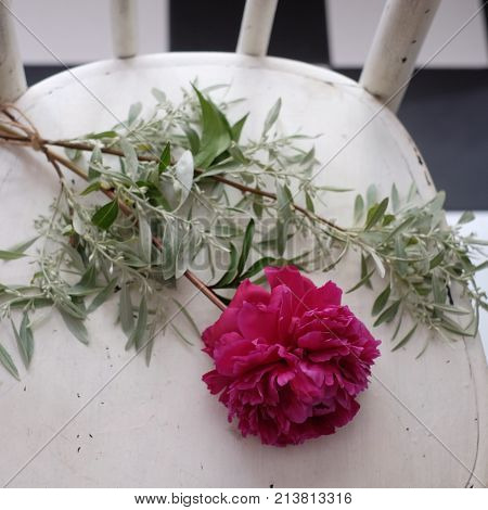 Bunch of peony flowers on white tablecloths with vintage wilted petals crumbled