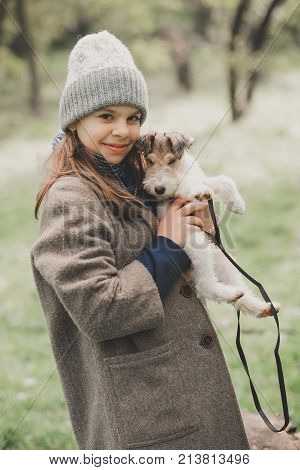 Girl playing with a dog fox terrier Outdoor