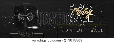 Black friday sale cardboard box tied with a black ribbon bow and lying on a black background with confetti and inscription Black friday Top view Template for the wide poster, banner and web.