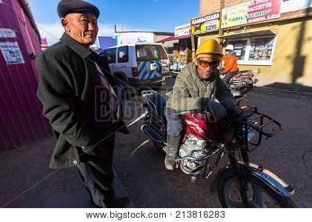 OLGIY, BAYAN-OLGIY, MONGOLIA - SEP 29, 2017: Motorcycle taxi driver waiting for customers near the city market. In Bayan-Olgiy province is populated to 88,7% by Kazakhs.