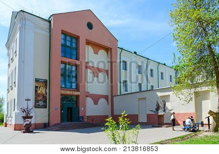POLOTSK BELARUS - MAY 19 2017: Unknown people are near building of Art Gallery and monument to Krivichi - founders of Polotsk Belarus