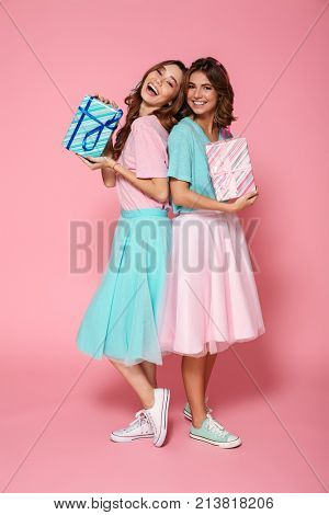 Two cheerful brunette woman in colorful clothes standing back to back and holding gift boxes, looking at camera, isolated on pink background