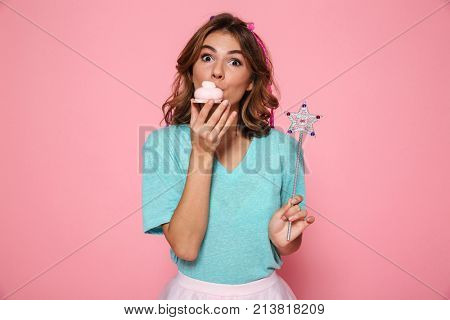 Close-up photo of pretty young girl with magic wand eating delicious cupcake, looking at camera, isolated over pink background