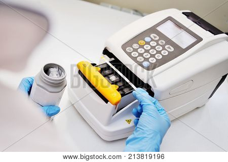 A doctor or lab assistant makes a urine test on a urine analyzer