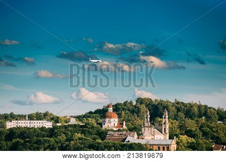 Vilnius, Lithuania. Plane Flying Over Church Of The Ascension And Church Of The Sacred Heart Of Jesus Among Green Foliage. Destination Scenic. UNESCO World Heritage. Famous And Popular Place.