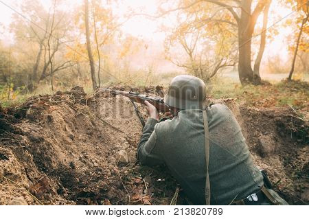 Unidentified Re-enactor Dressed As German Wehrmacht Infantry Soldier In World War II Hidden Sitting With Rifle Weapon In An Ambush In Trench In Autumn Forest At Sunset Or Sunrise poster