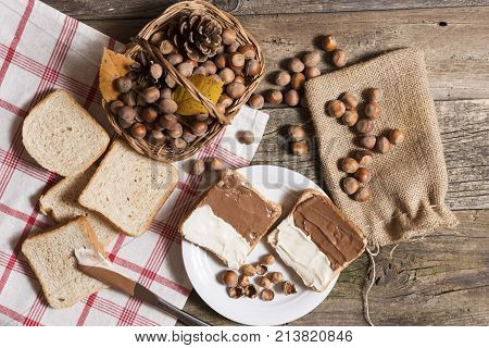 sliced bread with nutella cream on wooden table. hazelnuts on table