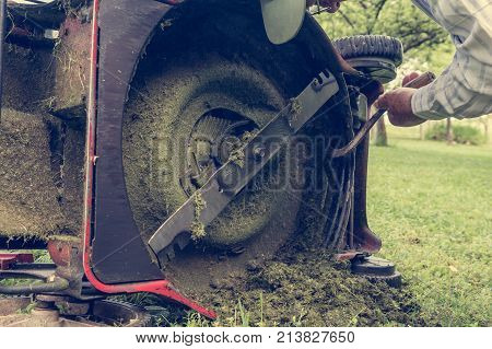 Man cleaning lawn mower blade. Preparing to mow some grass.