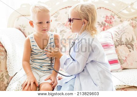 Portrait of serious little girl wearing glasses and lab coat playing doctor with brother her brother at home. Health and childhood concept