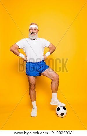 Full Length Of Modern Cool Funny Competetive Pensioner, Leader, Champion With His Foot On A Ball. Bo