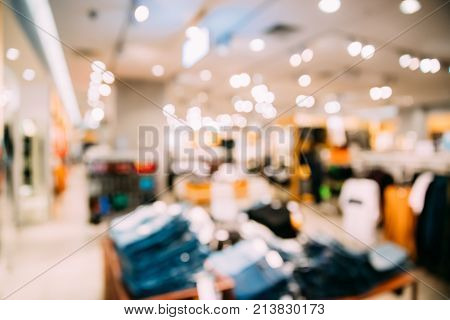 Blured Bokeh View Of Clothes On Shelves And Hanger In Store Of Shopping Center.