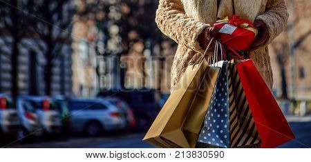 Rediscovering things everybody love in Milan. elegant tourist woman with shopping bags and Christmas gift near Sforza Castle in Milan Italy looking aside
