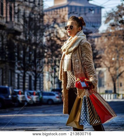 Rediscovering things everybody love in Milan. young tourist woman with shopping bags and Christmas gift near Sforza Castle in Milan Italy looking into the distance and walking