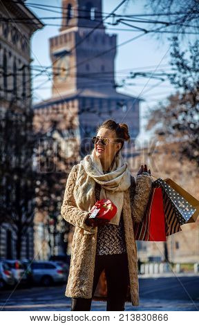 Rediscovering things everybody love in Milan. happy young woman with shopping bags and Christmas gift near Sforza Castle in Milan Italy looking into the distance