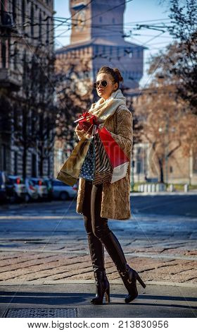 Rediscovering things everybody love in Milan. Full length portrait of modern tourist woman with shopping bags and Christmas gift in Milan Italy walking