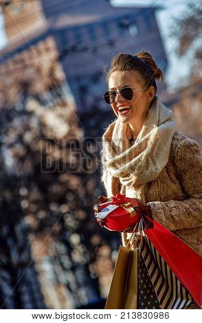 Rediscovering things everybody love in Milan. smiling trendy traveller woman with shopping bags and Christmas gift in Milan Italy looking into the distance