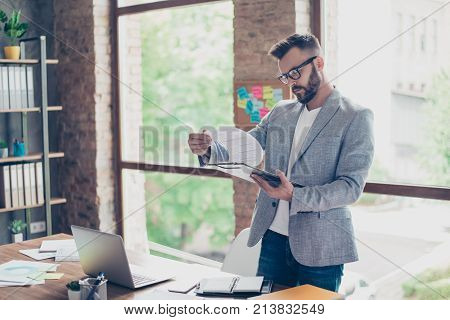 Focused Concentrated Accountant, Fashionable Brunet Bearded Guy Is Looking At The Report, Stands In