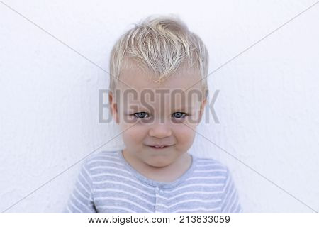 Emotions. Shy toddler against wall. Close-up portrait of cute little boy.