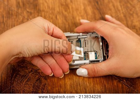 the insertion of the SIM card in a smartphone on wooden table. girl inserts a SIM card in the phone