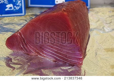 Fresh and raw big tuna fish was cut into pieces by the expert fishmonger for showing to the customer at the fresh and clean market.