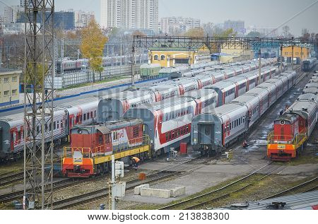 MOSCOW, RUSSIA, OCT,26, 2017: Russian Railways passenger trains in Rizhskaya depot under maintenance. Passenger train depot. RZD passenger coaches cars Train coaches roofs Shunter locomotive depot MOT