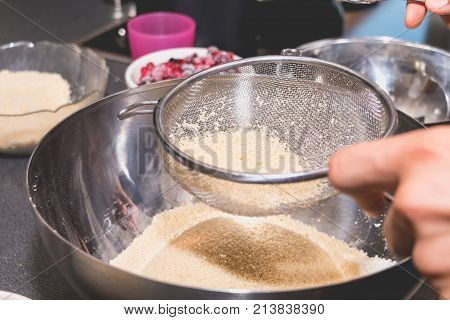 Cook Mixes And Sieves Almond Powder In Flour